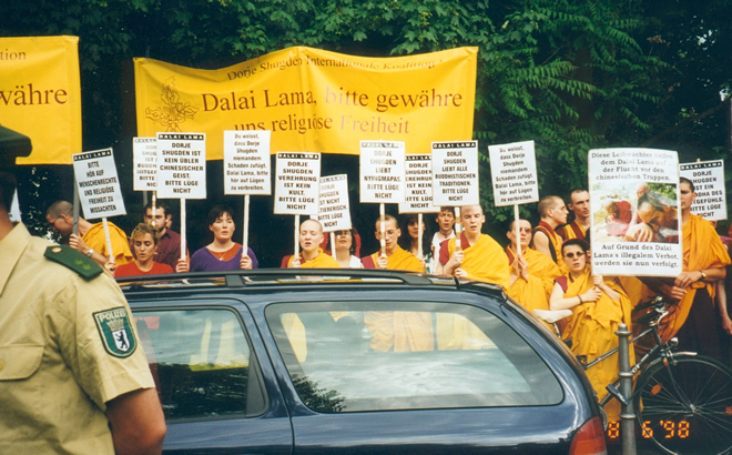 Berlin, Tempodrom, 8th June 1998. From 1996–1998 the New Kadampa Tradition organised world wide protests via Shugden Supporters Community (SSC). The big yellow banner reads: 'Dalai Lama, please grant us religious freedom.' From left to right the signs read (signs with the same slogan are listed only once): 'Please stop ignoring human and religious freedom', 'Dorje Shugden is a Buddha of compassion, please don't lie', 'Dorje Shugden is no wicked Chinese spirit, please don't lie', 'You know that Dorje Shugden doesn't harm anybody, Dalai Lama please stop to spreading lies', 'Dorje Shugden worship is no cult, please don't lie', 'Dorje Shugden is not sectarian, please don't lie', 'Dorje Shugden loves Nyingmapas, please don't lie', 'Dorje Shugden loves all Buddhist traditions, stop spreading lies', 'You know that Dorje Shugden doesn't harm anybody, Dalai Lama please stop spreading lies', 'These bodyguards helped the Dalai Lama on his escape from Chinese troops based on the Dalai Lama's illegally ban they are now persecuted'.